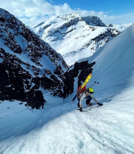 Ski mountaineer climbing a steep snowy slope