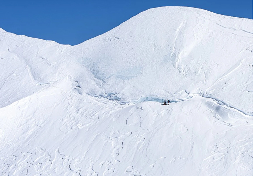 Two small figures on the snowy flank of Mt. Steele, on the way to Lucania