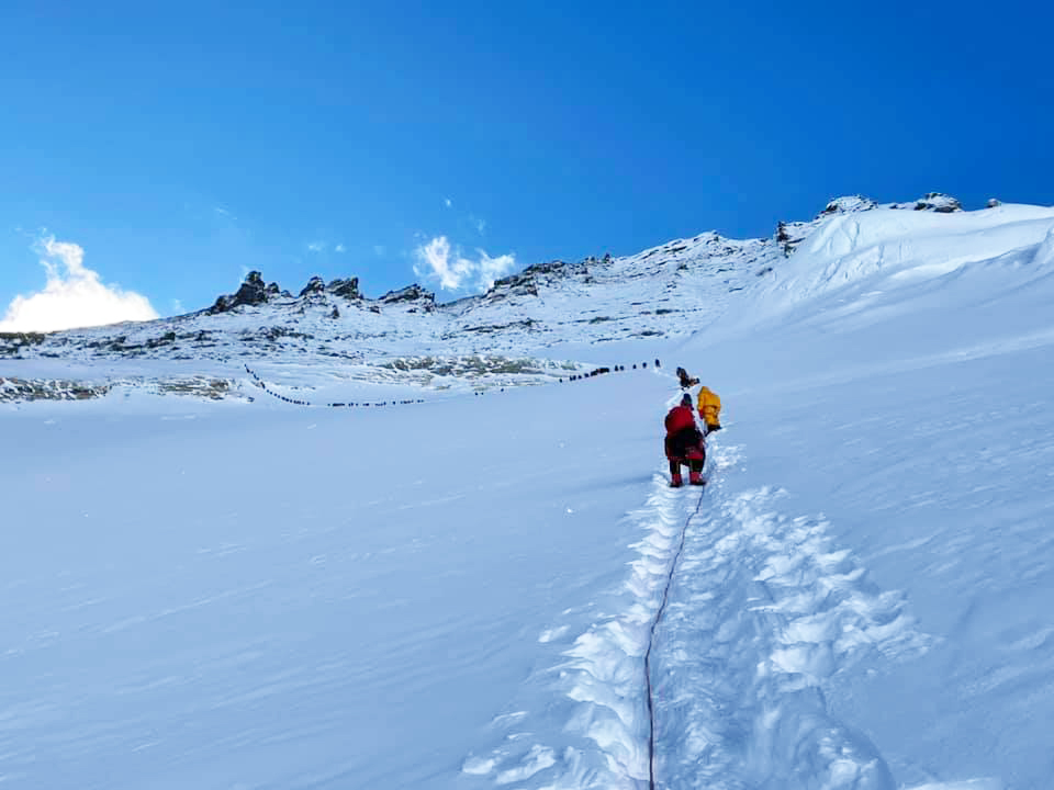 A crowded line of climbers moving up a snowy flattish area on Everest.