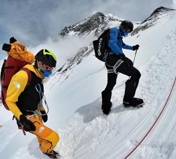 Two climbers wearing air-filtering masks move up Everest