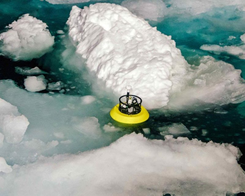 A device in the water, amid pieces of sea ice, measures underwater warm areas.