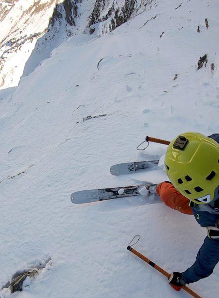 Skiers poised on edge of steep couloir