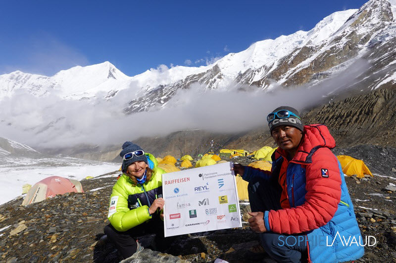 Woman climber and Sherpa holding sponsors' sign.