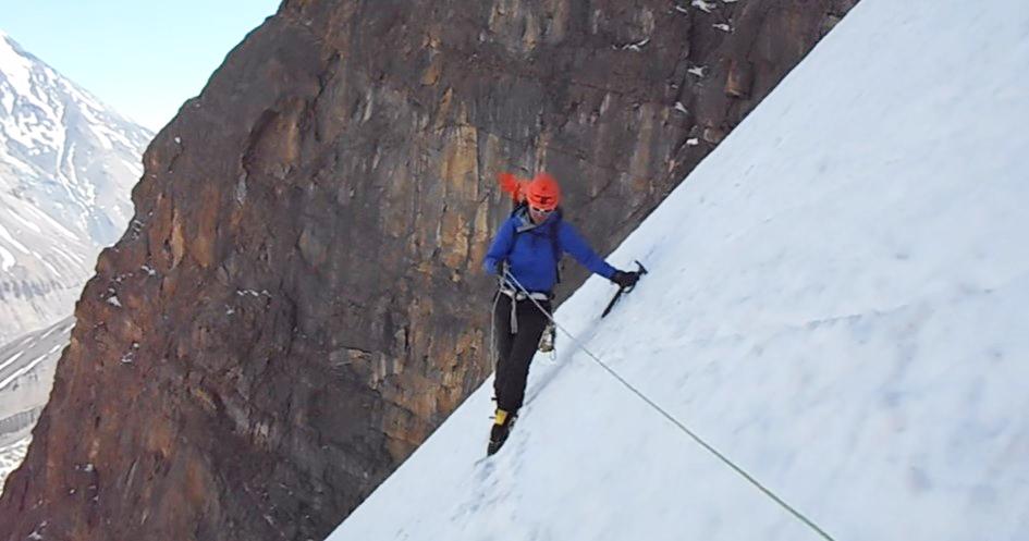 Climber traversing a steep snowy ridge