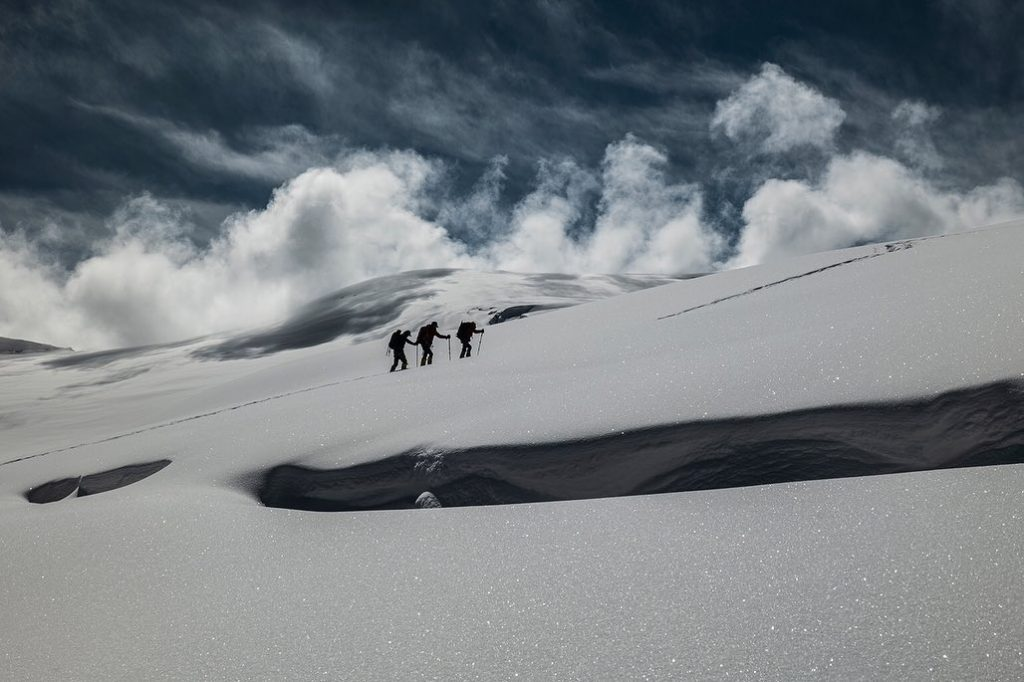 Three climbers moving up a snowy slope on Dhaulagiri