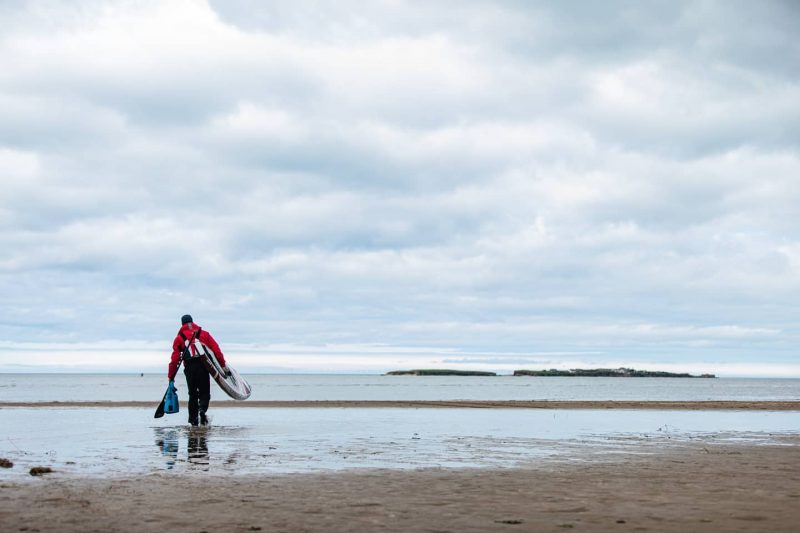 Man carries SUP into the ocean