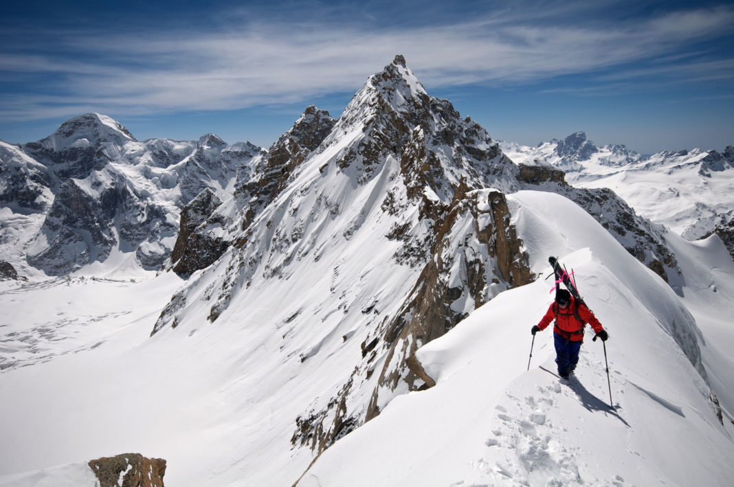 Mountaineer with skis on back along airy ridge
