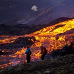People stand before a river of lava
