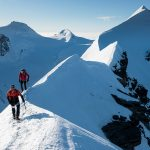 Two mountaineers on an airy, snowy ridge